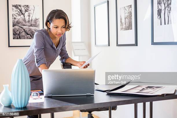 Black businesswoman using laptop in art gallery office