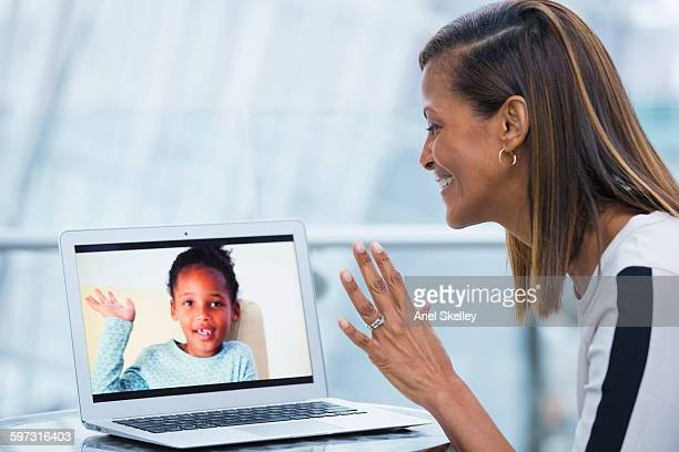 Black businesswoman video chatting with daughter