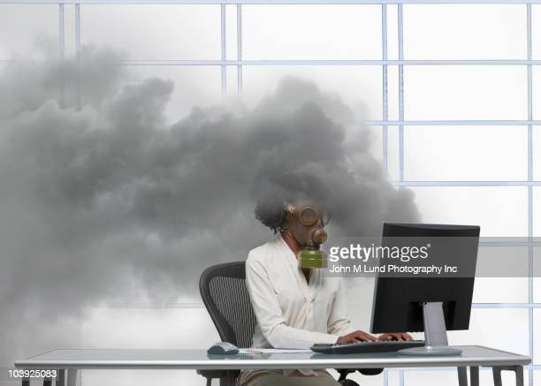 Black businesswoman wearing gas mask at smoking computer