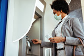 Black businesswoman wearing protective mask while withdrawing money at ATM.