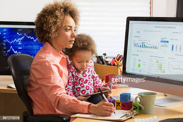 Black businesswoman with daughter working at home