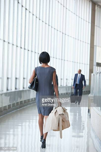 Black businesswoman with luggage walking in airport