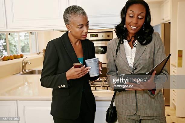Black businesswomen talking in kitchen