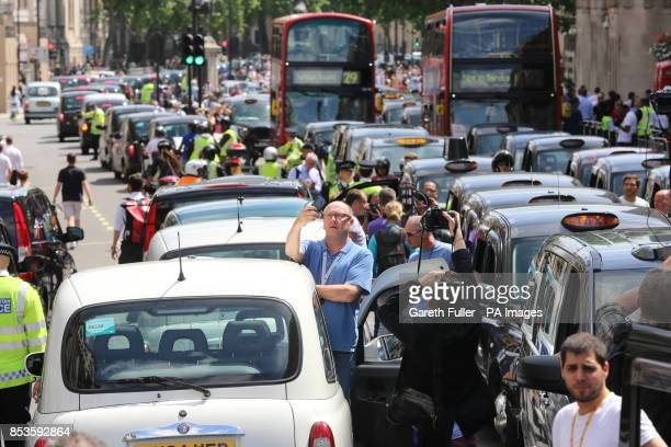 Black cab and licensed taxi drivers protest at Trafalgar Square London over the introduction of a phone app called Uber which allows customers to...