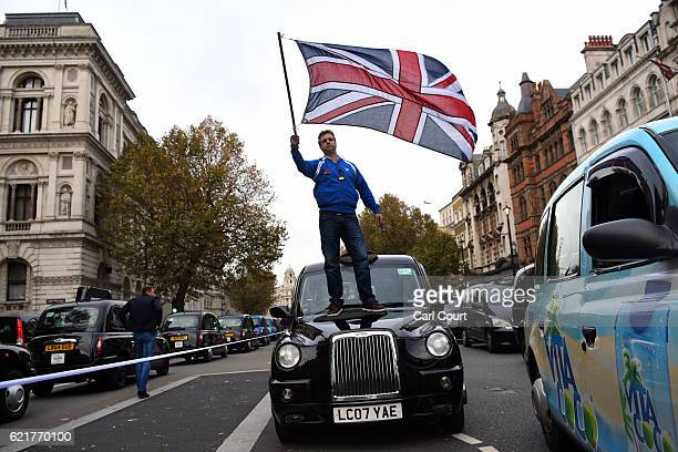 A black cab driver waves a Union flag as he takes part in a protest to highlight congestion and air pollution on November 8 2016 in London England...
