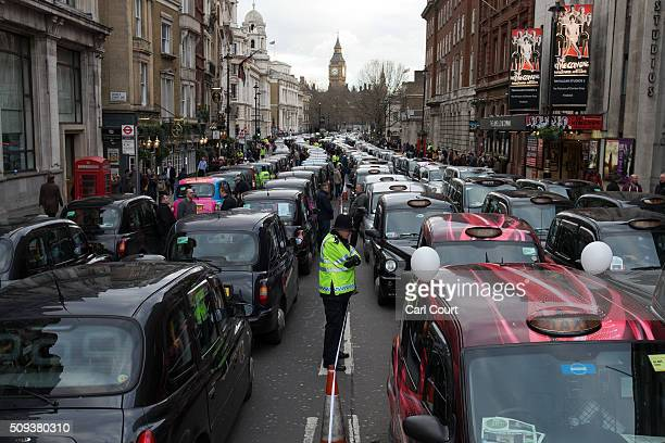 Black Cab drivers block Whitehall as they take part in a protest against Uber on February 10 2016 in London England Drivers are claiming that Uber is...