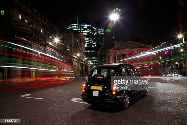 Black cab stops still in the centre of a busy traffic junction at night in London - light trails by London buses can be seen as they seem to float...