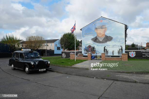 A black cabbie tourist taxi drives past a Union Jack flag seen amass at the memorial site of Stevie McKeag also known as TopGun who was a Loyalist...