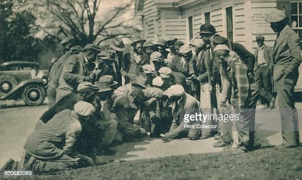 'Black Caddies Playing Craps' c1920s. African American golf caddies playing craps. From a postcard titled 'Forrest Hills-Ricker Hotel, Augusta, GA:...