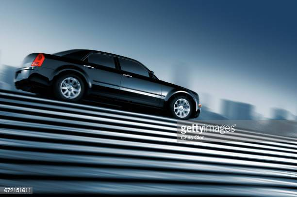 Black car driving at top of urban staircase