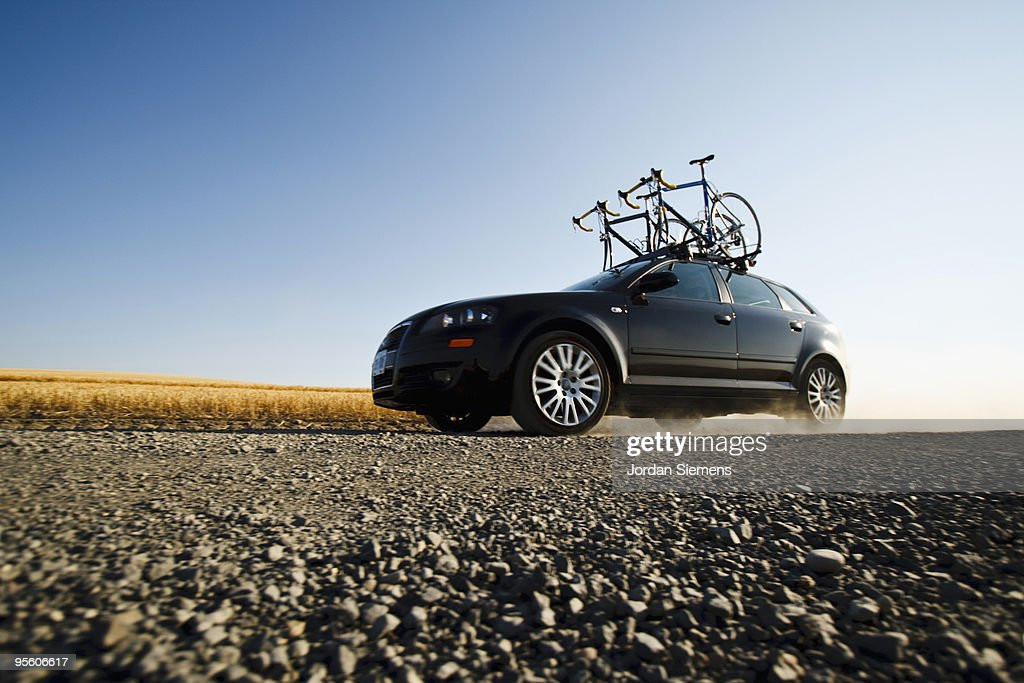 A black car with two road bikes on top cruises along a dirt road leaving a trail of dust in the dist : ストックフォト