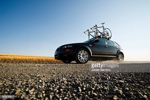 A black car with two road bikes on top cruises along a dirt road leaving a trail of dust in the dist