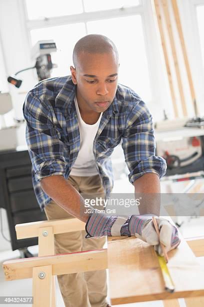 Black carpenter measuring wood in shop