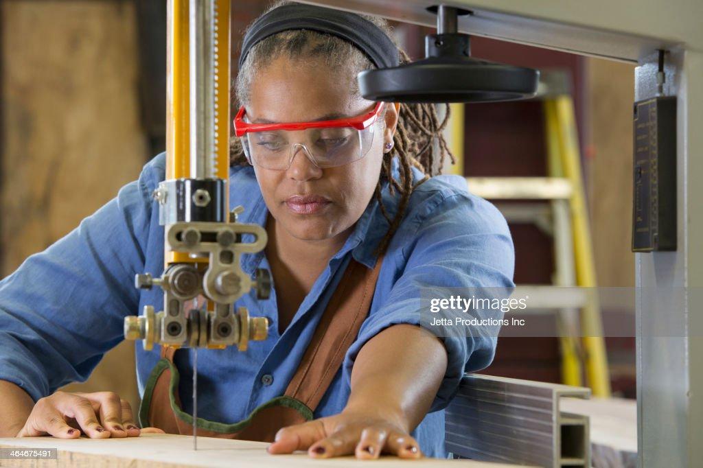Black Carpenter Using Cutting Machine In Workshop Stock Photo