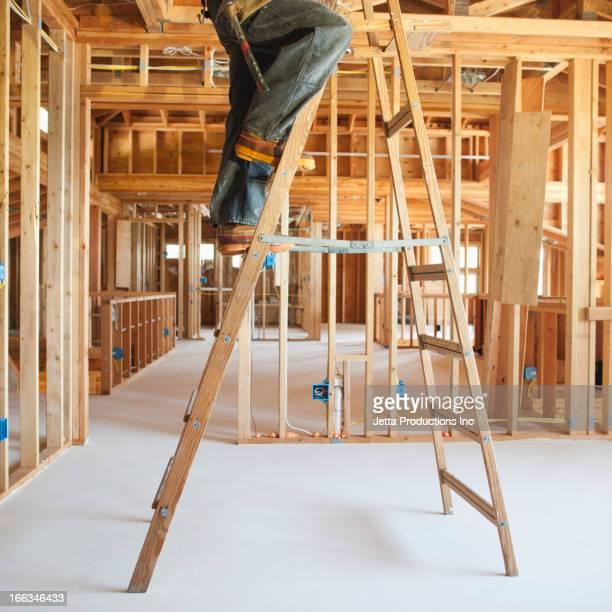 Black carpenter working on ceiling of unfinished room