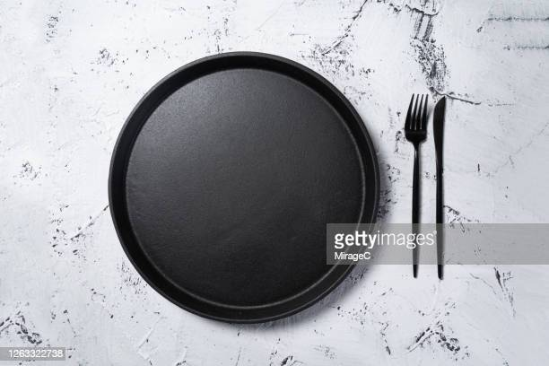 black cast iron plate pan with eating utensil - plate stock pictures, royalty-free photos & images