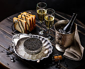 Black caviar in can on ice in silver bowl, bread and champagne in ice bucket