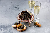 Black caviar in silver bowl, sandwiches and champagne