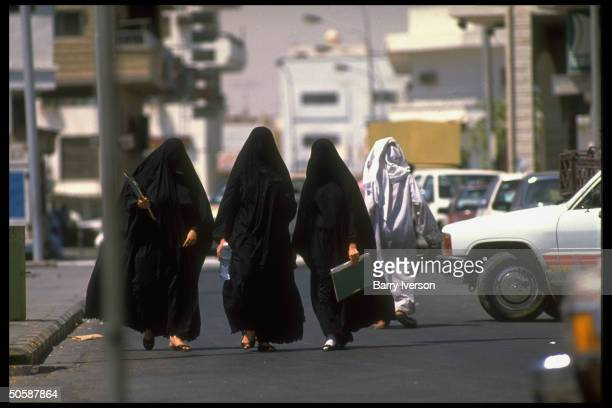 Black chadorenveloped women displaying modesty mandated by Islamic conventions 1 carrying bottled water out strolling Saudi Arabia