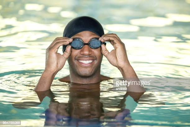 Black cheerful young man putting on the swimming goggles looking at camera very happy at the pool