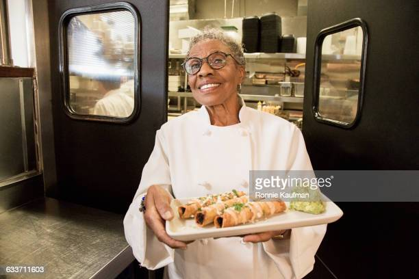 Black chef holding plate of food in restaurant