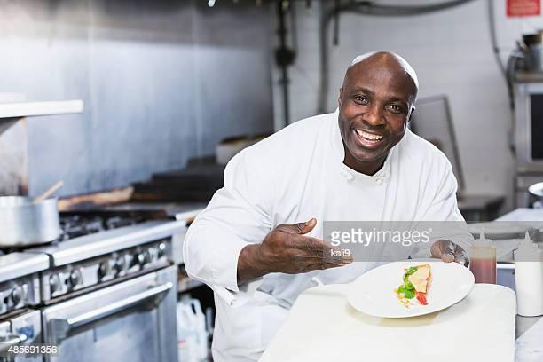 Black chef in a restaurant holding dessert plate