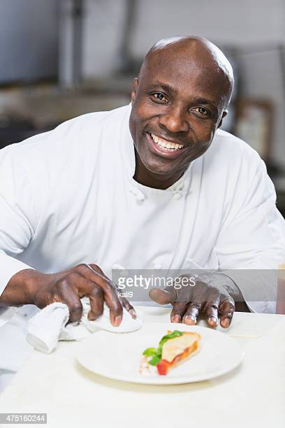 Black chef in a restaurant plating food