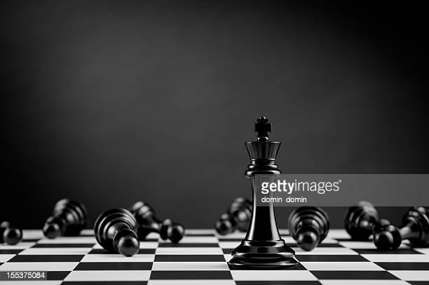 Black Chess King among lying Pawns on chessboard