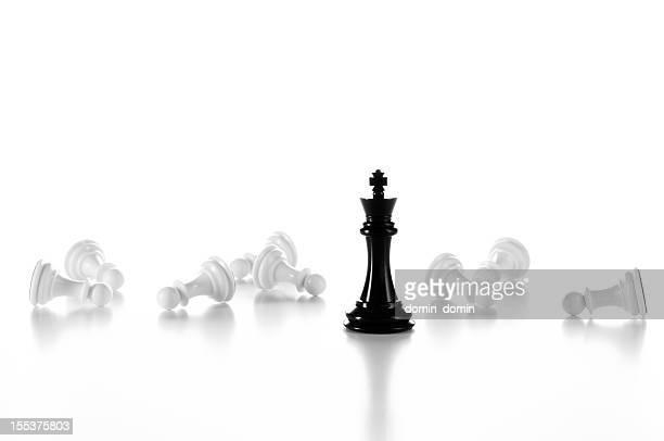 Black Chess King among lying white Pawns, isolated on white