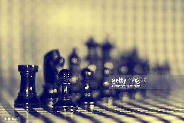 Black chess pieces on a checkered background