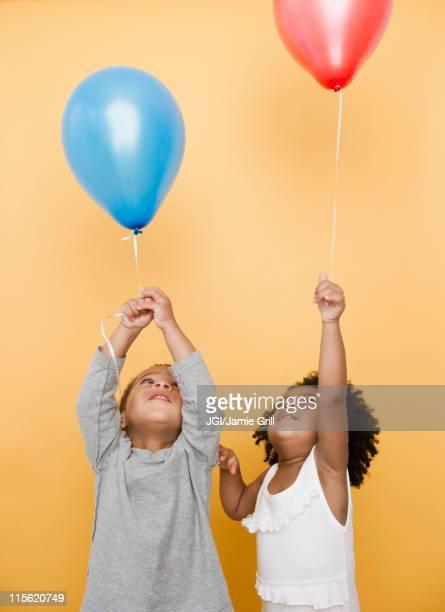 Black children holding helium balloons