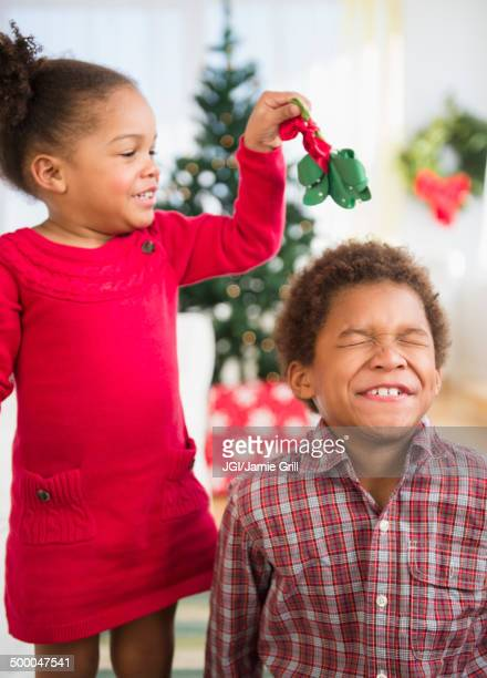 black children playing with mistletoe in living room - gui photos et images de collection