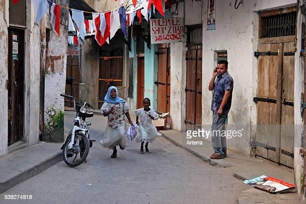 Black children running in alley of the old medina of Stone Town / Stonetown / Mji Mkongwe Zanzibar Tanzania East Africa