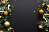 Black Christmas background with golden decorations, baubles, fir tree branches, confetti. Christmas holiday celebration, winter, New Year concept. Christmas banner mockup, greeting card template.