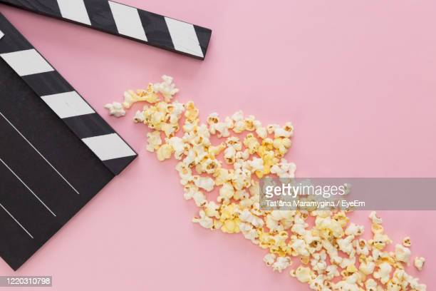 black clapper board and popcorn on a colored background with free space for text - film industry stock pictures, royalty-free photos & images