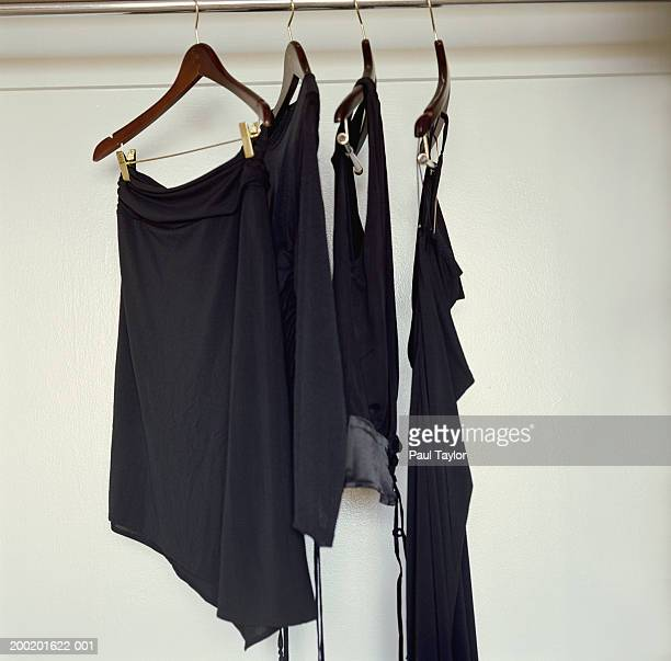 Black clothing hanging from hangers in closet