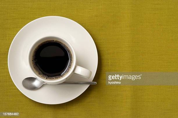 Black coffee and spoon on green tablecloth with copy space