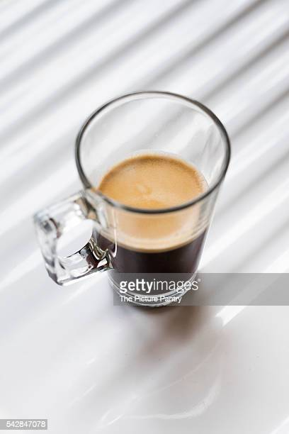 Black coffee in a clear glass mug on a white background