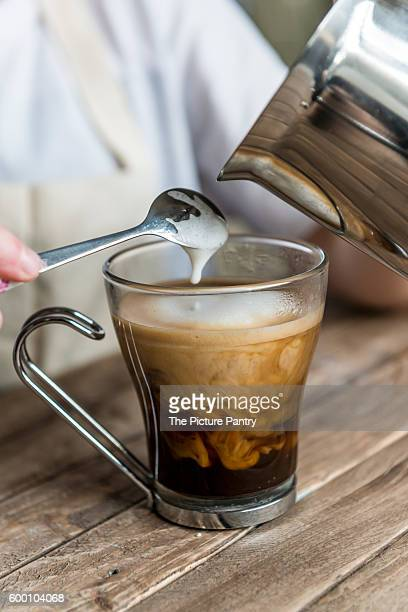 A black coffee. Milk being poured in to a coffee by a barista.