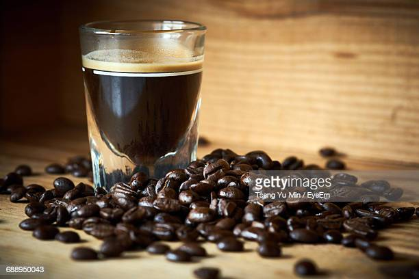 Black Coffee With Roasted Beans On Table