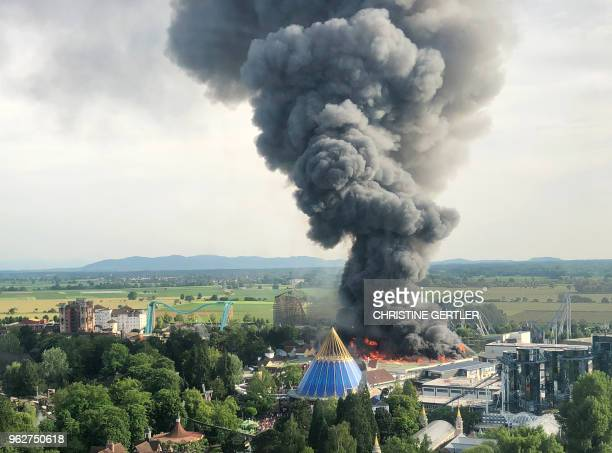 A black column of smoke rises from a warehouse in flames above the amusement park 'Europapark' in Rust southern Germany on May 26 2018 A fire has...