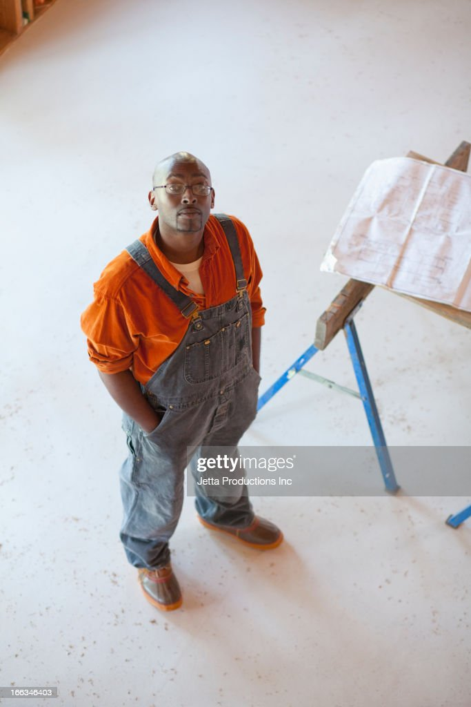 Black construction worker standing in unfinished room : ストックフォト