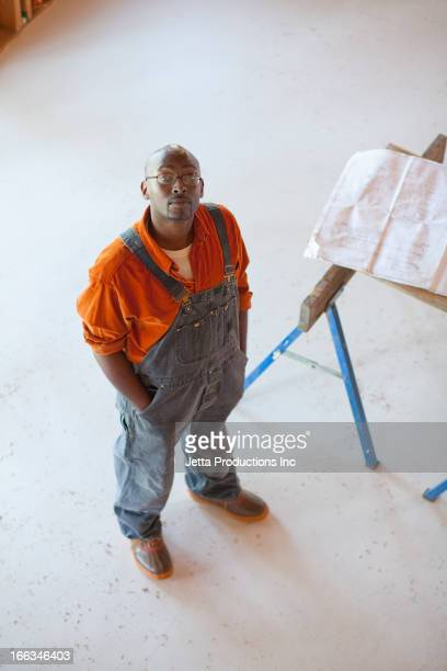 black construction worker standing in unfinished room - ジャンプスーツ ストックフォトと画像