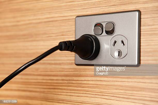 A black cord plugged into a power point on a wooden wall