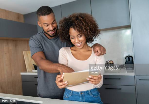 black couple at home checking their mail - mail stock pictures, royalty-free photos & images