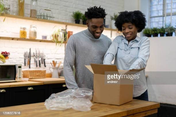 black couple at home opening a parcel in the mail - examining stock pictures, royalty-free photos & images
