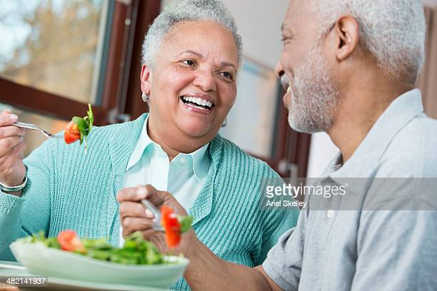 black couple eating salad - fat woman sitting on man stock pictures, royalty-free photos & images