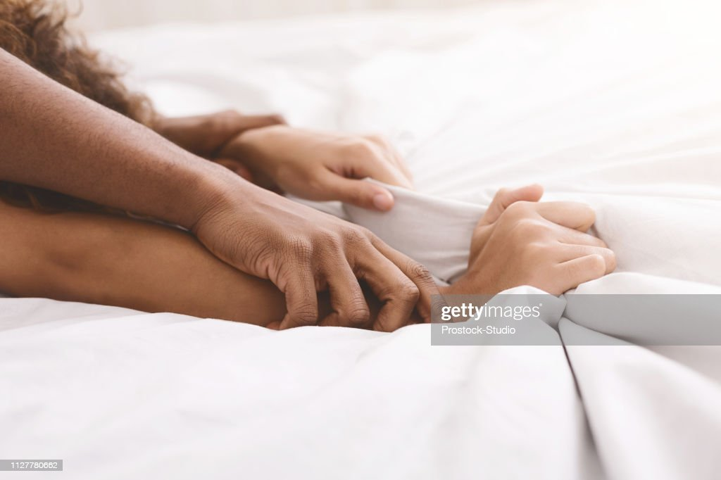 Black couple hands pulling white sheets in ecstasy : Stock Photo