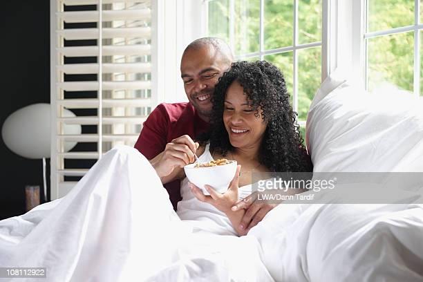 Black couple having breakfast in bed