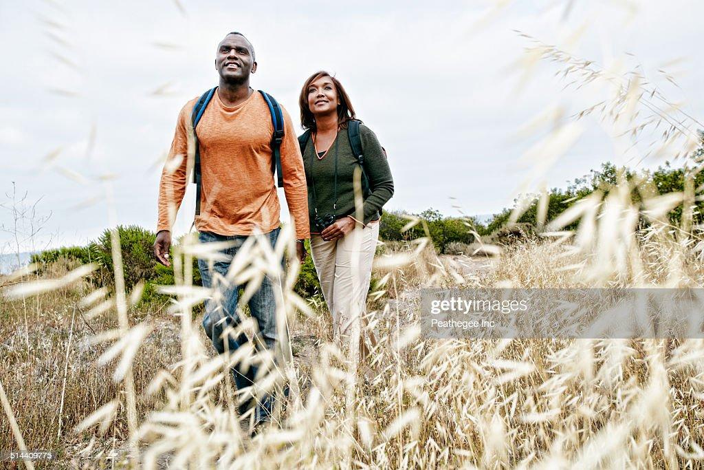 Black Couple Hiking On Rural Hillside Stock Photo